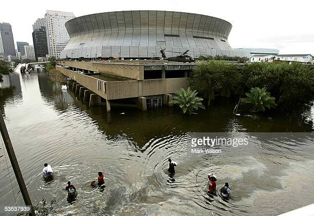 People walk through high water in front of the Superdome August 30 2005 in New Orleans Louisiana Thousands of people are left homeless after...