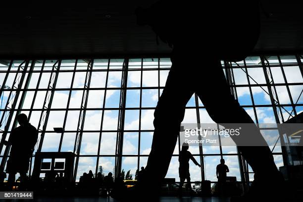 People walk through international arrivals at terminal four at John F Kennedy airport following an announcment by the Supreme Court that it will take...