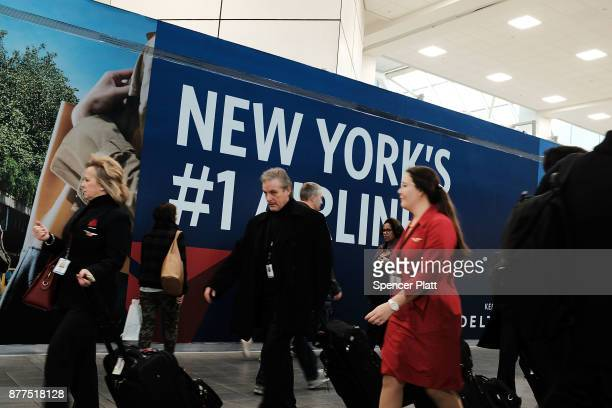 People walk through LaGuardia Airport on the day before Thanksgiving the nation's busiest travel day on November 22 2017 in New York New York...