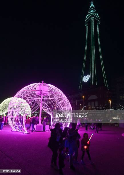 People walk through light installations in front of the Blackpool Tower during the Blackpool Illuminations in Blackpool, north west England on...
