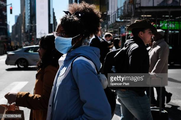 People walk through Manhattan with surgical masks as fears of the coronavirus spreading through the US increase on March 04 2020 in New York City...