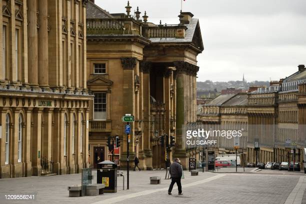 People walk through near-deserted streets in the centre of Newcastle upon Tyne, Thursday lunchtime in north-east England on April 9, 2020 as Britain...