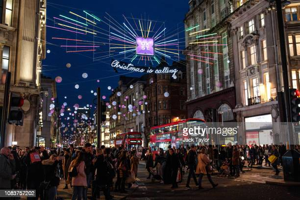 People walk through Oxford Circus as Christmas lights hang from above on December 17 2018 in London England Fewer shoppers are hitting the High...