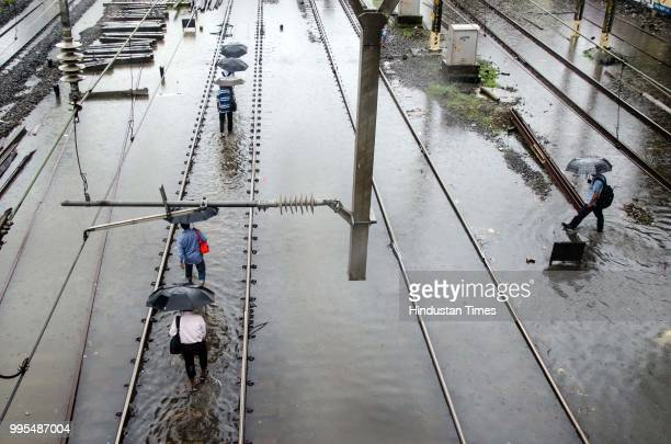 People walk through railway tracks at Parel on July 9 2018 in Mumbai India Indias financial capital and its surrounding districts were in for another...