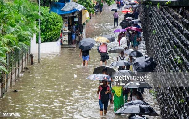 People walk through rain water at Parel local railway station on July 9 2018 in Mumbai India Indias financial capital and its surrounding districts...