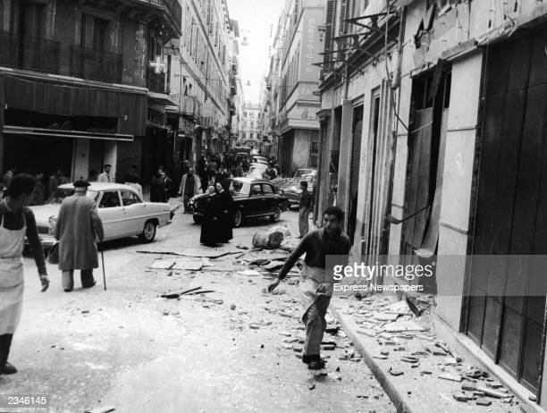 People walk through rubble on the bombedout streets of Algiers following the plastic bombing of Arabowned shops by the French Secret Army Algeria...