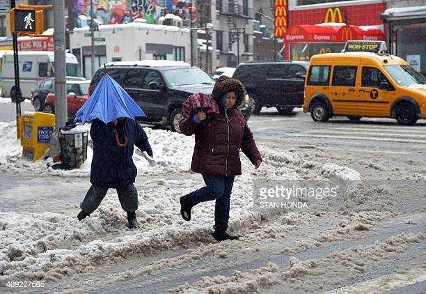 People walk through slush on a corner in the Greenwich Village area of Manhattan February 13 2014 in New York Up to a foot of snow is expected in the...