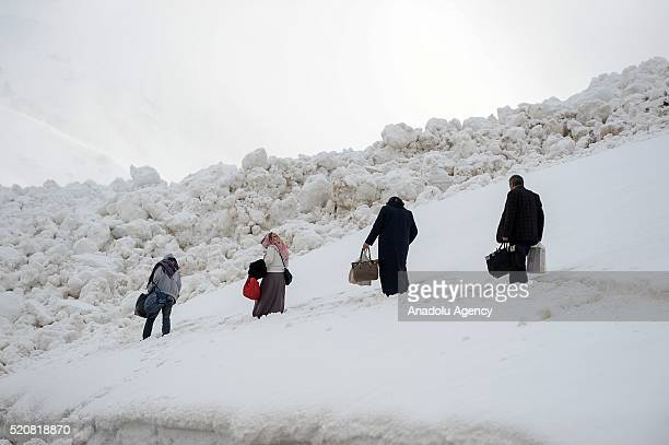 People walk through snow due to the heavy snow fall closing the road at Karabet Gateway in Bahcesaray district of Van on April 12 2016 In order to...