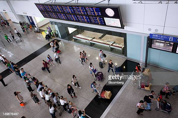 People walk through the arrival hall of Chek Lap Kok Airport in Hong Kong China on Sunday Aug 5 2012 The number of overseas visitors to Hong Kong...
