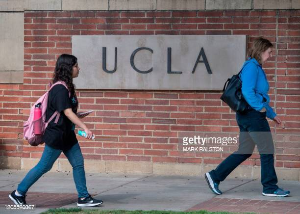 People walk through the campus of the UCLA college in Westwood, California on March 6, 2020. - Three UCLA students are currently being tested for the...
