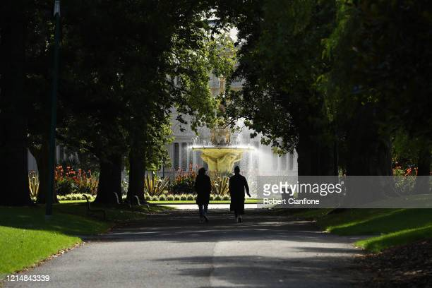 People walk through the Carlton Gardens on March 26, 2020 in Melbourne, Australia. Further restrictions on travel and movement have been put in to...