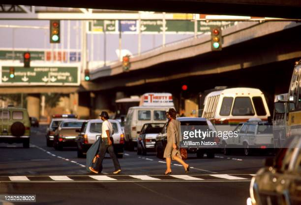 People walk through the crosswalk on their way to the terminal circa August 1983 at the Los Angeles International Airport in Los Angeles California