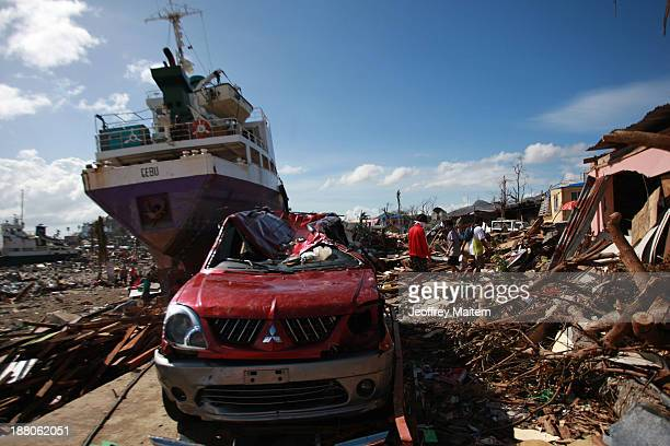 People walk through the debris caused by the typhoon in Tacloban on November 15 2013 in Tacloban Philippines Typhoon Haiyan which ripped through...