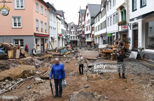 People walk through the debris in the pedestrian zone in Bad Muenstereifel, western Germany, on July 16 after heavy rain hit parts of the country,...