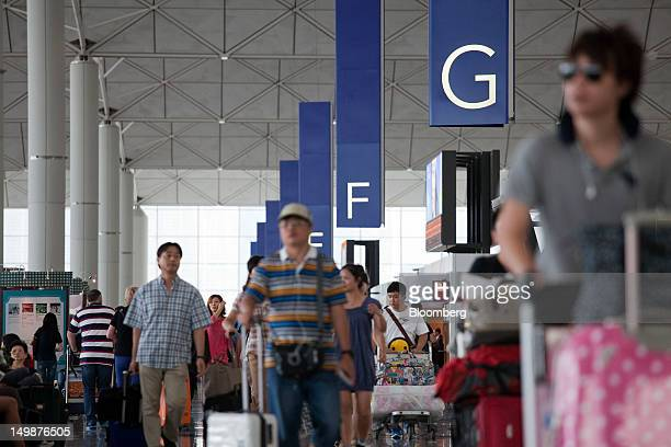 People walk through the departure hall of Chek Lap Kok Airport in Hong Kong China on Sunday Aug 5 2012 The number of overseas visitors to Hong Kong...
