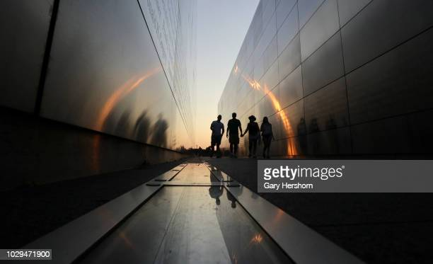 People walk through the Empty Sky 9/11 Memorial in Liberty State Park at sunset on August 28 2018 in Jersey City New Jersey