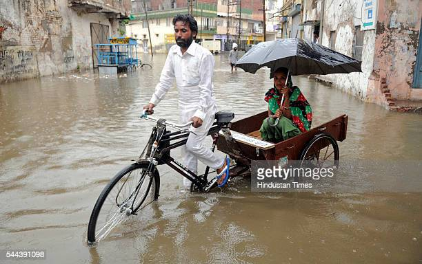 People walk through the flooded water after heavy rains at Khalsa Mohala Road on July 2 2016 in Patiala India The sudden rain on Saturday morning...