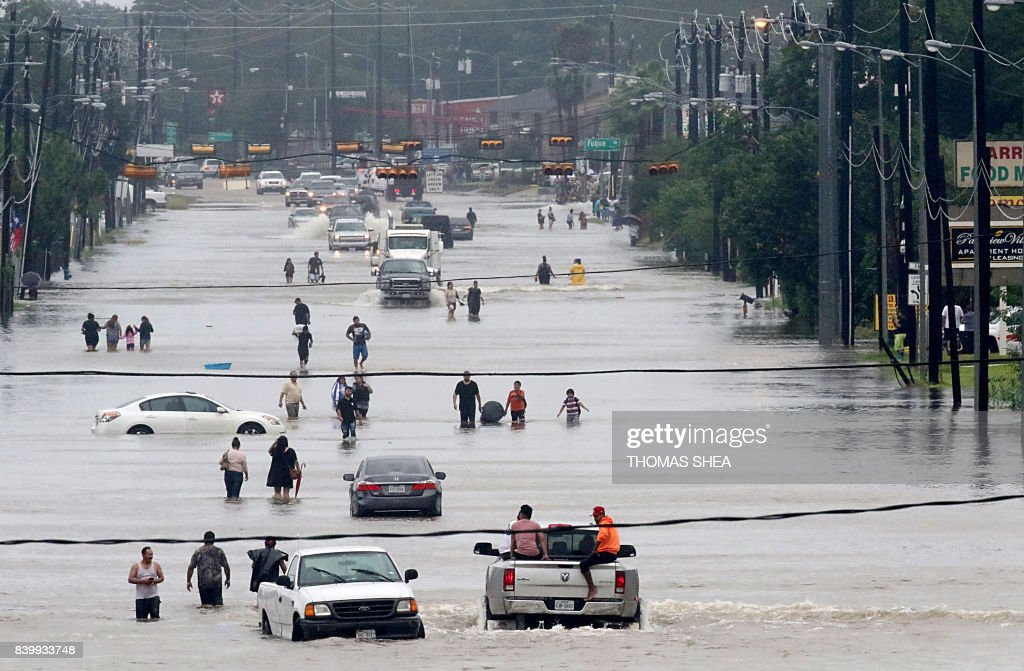 TOPSHOT - People walk through the flooded waters of Telephone Rd. in Houston on August 27, 2017 as the US fourth city city battles with tropical storm Harvey and resulting floods. / AFP PHOTO / Thomas B. Shea