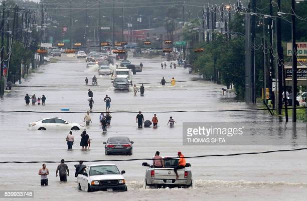 TOPSHOT People walk through the flooded waters of Telephone Rd in Houston on August 27 2017 as the US fourth city city battles with tropical storm...