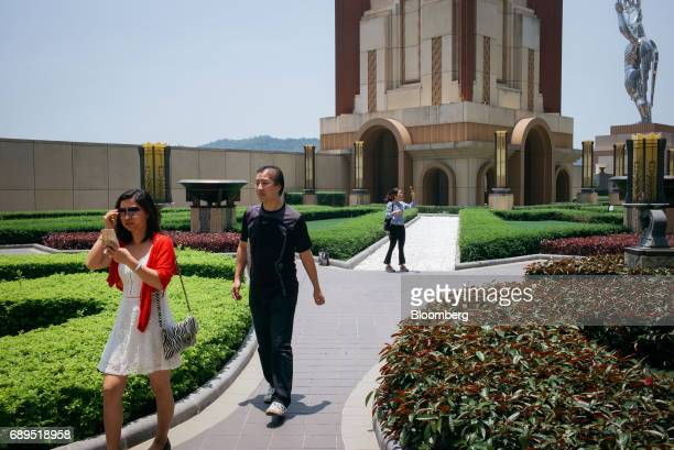 People walk through the French Garden at Studio City casino resort developed by Melco Crown Entertainment Ltd in Macau China on Thursday May 25 2017...