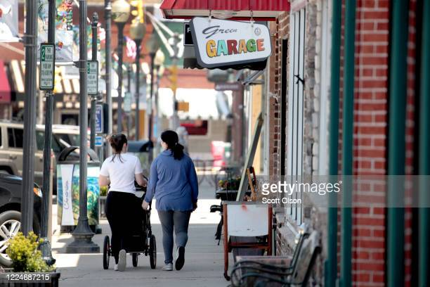 People walk through the historic downtown past businesses that mostly remain shuttered on May 13, 2020 in Chesterton, Indiana. Recently, Indiana...