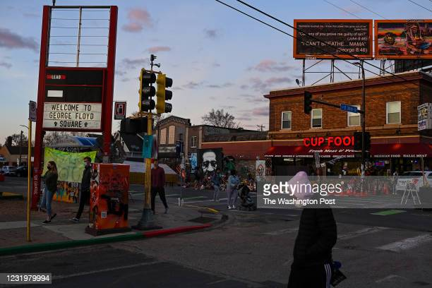 People walk through the intersection of 38th Street and Chicago Avenue, also known as George Floyd Square as the sun sets on March 25, 2021 in...