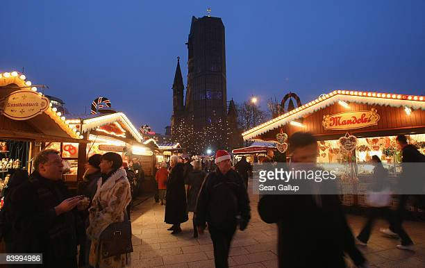 People walk through the Kurfuerstendamm Christmas market as the Kaiser Wilhelm Memorial Church stands behind on December 11 2008 in Berlin Germany...