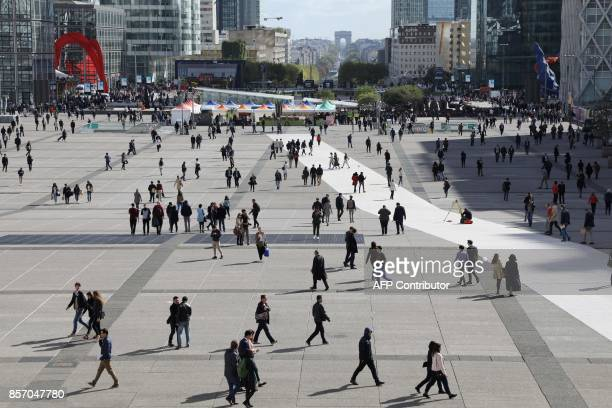 People walk through the La Defense business district in Courbevoie on October 3 2017 / AFP PHOTO / LUDOVIC MARIN