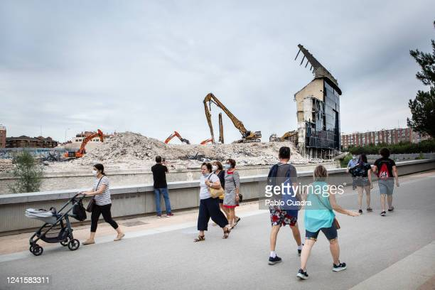 People walk through the Madrid Rio park viewing in the background the almost demolished Vicente Calderon historic stadium, Atletico Madrid's former...