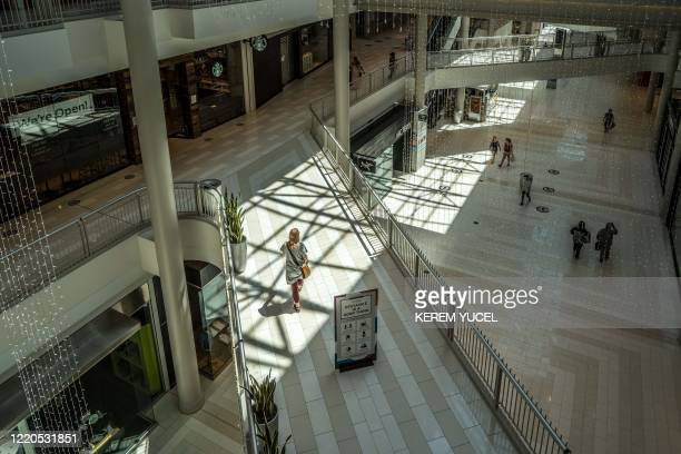 People walk through the Mall of America on June 16, 2020 in Bloomington, Minnesota, after some of the shops at the mall reopened on June 10. - The...