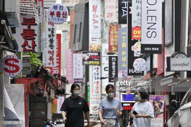 People walk through the Myeongdong shopping district in Seoul on August 27, 2020. - South Korea's central bank slashed its growth forecast on August...