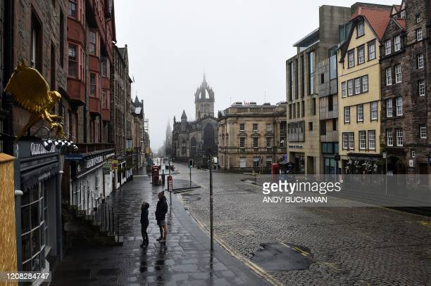 People walk through the near deserted streets of Edinburgh, Scotland on March 26, 2020 after the government ordered a lockdown to help stop the...