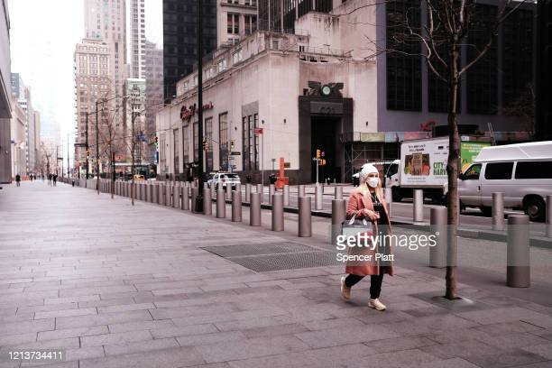 People walk through the nearly empty streets in lower Manhattan on March 20, 2020 in New York City. Schools, businesses and most places where people...