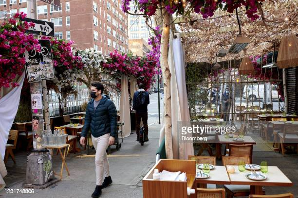 People walk through the outdoor seating area at Lola Taverna restaurant in New York, U.S., on Wednesday March 10, 2021. Cash-strapped landlords are...