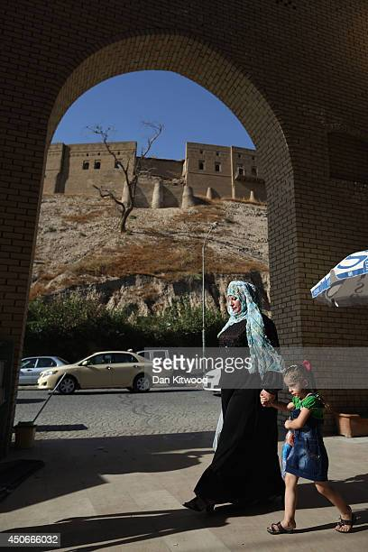 People walk through the Qaysari Market next to the ancient Citadel on June 15 2014 in Erbil Iraq The Citadel is thought to be the oldest continuously...