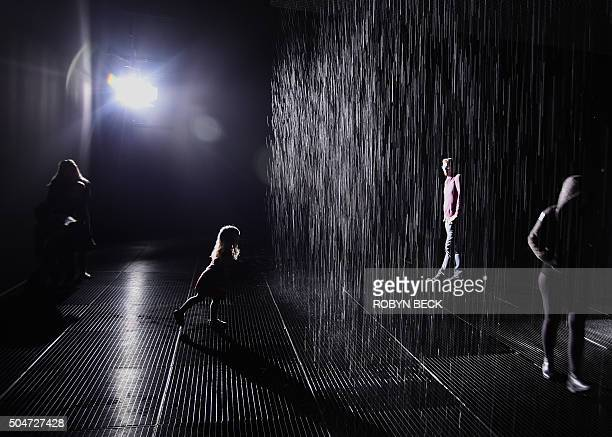 People walk through the Rain Room exhibition by the artists' collective Random International at the Los Angeles County Museum of Art in Los Angeles...