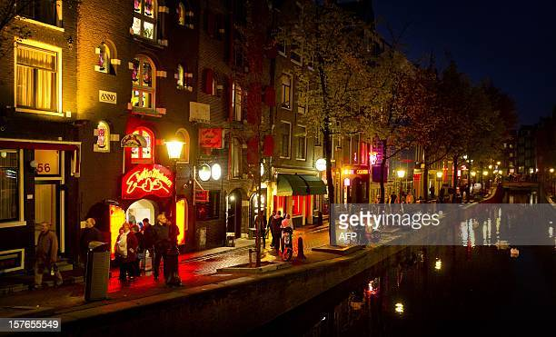 People walk through the redlight district known as De Wallen in Amsterdam on October 13 2011 De Wallen is the largest redlight district situated in...