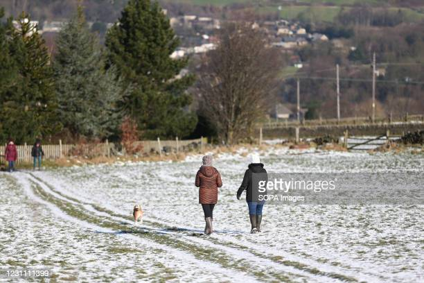People walk through the remaining snow as the Sun shines in West Yorkshire. There have been several days of cold weather and persistent snowfall...