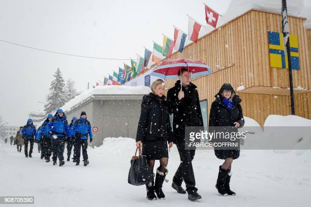 People walk through the resort town of Davos as snow falls ahead of the World Economic Forum 2018 annual meeting on January 22 2018 in Davos eastern...