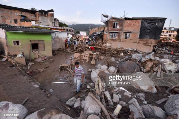People walk through the rubble left by mudslides following heavy rains in Mocoa Putumayo department southern Colombia on April 1 2017 Massive...