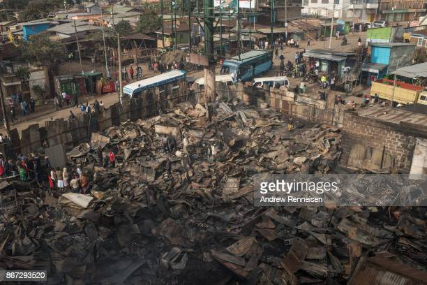 People walk through the ruins of Kikuyu homes and shops which were destroyed in the Kawangware slum on October 28 2017 in Nairobi Kenya Protests...