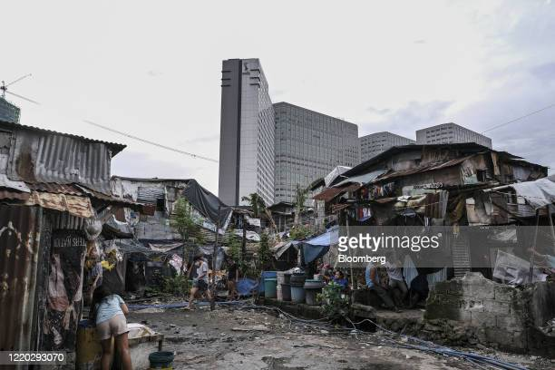 People walk through the San Roque neighborhood as commercial high-rise buildings stand in the background in Quezon City, Metro Manila, the...