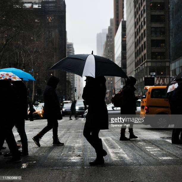 People walk through the snow and sleet in Manhattan on February 12 2019 in New York City New York City in a winter that has been light on snow this...