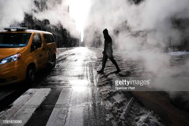 People walk through the snow in Manhattan on December 17, 2020 in New York City. New York City received 6 to 8 inches of snow in an overnight storm...