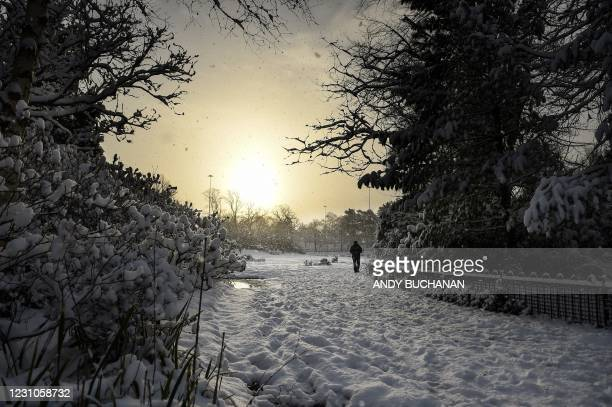 People walk through the snow in Victoria Park in Glasgow on February 9, 2021. - Cold weather swept across northern Europe bring snow and ice.