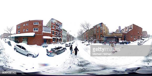 People walk through the snow on January 23 2016 in the Brooklyn borough of New York City The Northeast and parts of the South are experiencing heavy...
