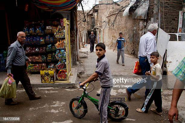 People walk through the street in a reidential neighborhood, March 18, 2013 in Baghdad, Iraq. Ten years after the regime of Saddam Hussein was...