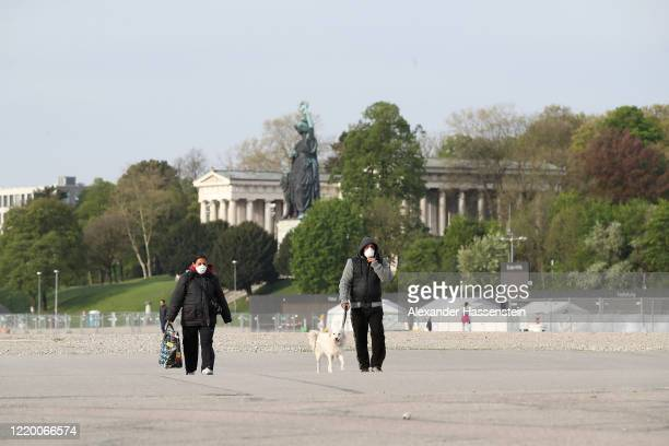 People walk through the Theresienwiese meadow, the site of the annual Oktoberfest beer fest, in front of the of the ensemble of the Bavaria statue, a...