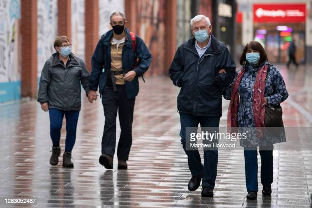 People walk through the town centre wearing face masks on October 30, 2020 in Newport, Wales. Wales entered a national lockdown on October 23 which...
