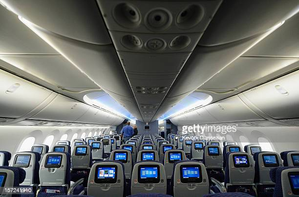 People walk through the United Airlines Economy Class with personal entertainment systems, with 13 languages available, on the new Boeing 787...
